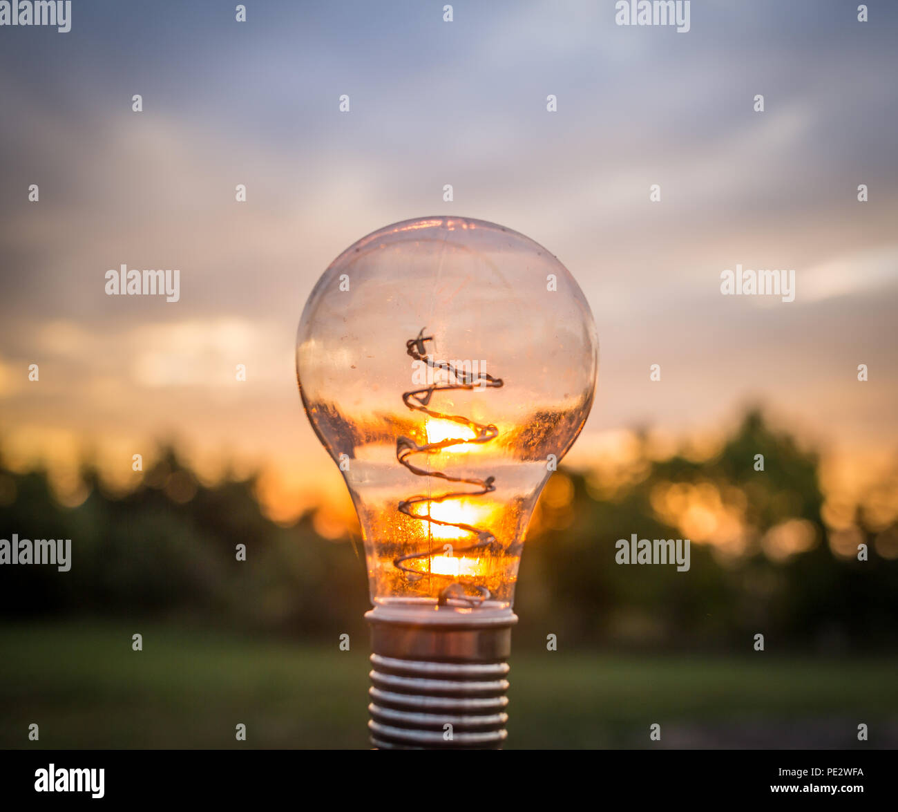 A light bulb outside during a sunset. - Stock Image