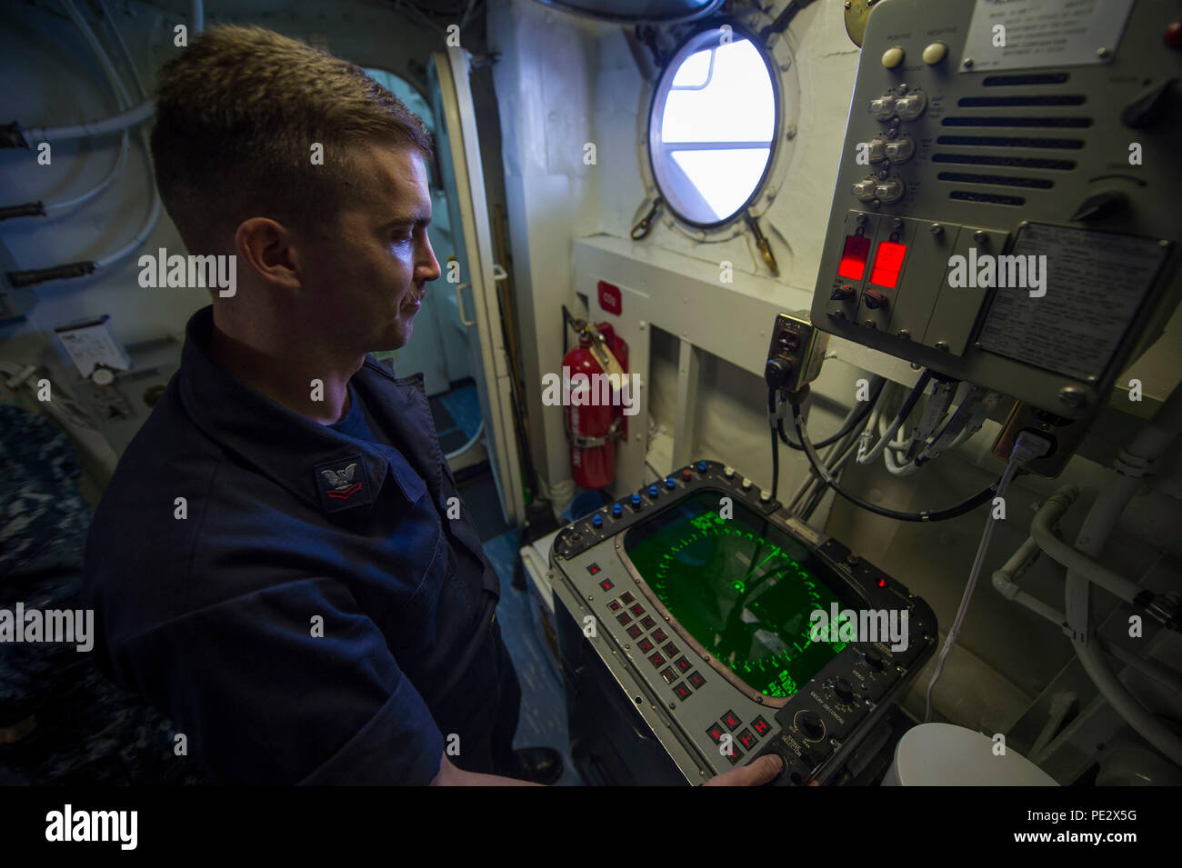 ARABIAN GULF (Sept. 23, 2015) Aerographer's Mate 2nd Class Aaron Radosevich monitors a SPA 25G radar for adherent weather conditions in the meteorological and oceanographic (METOC) office of Wasp-class amphibious assault ship USS Essex (LHD 2). Essex is the flagship of the Essex Amphibious Ready Group (ARG) and, with the embarked 15th Marine Expeditionary Unit (MEU), is deployed in support of maritime security operations and theater security cooperation efforts in the U.S. 5th Fleet area of operations. (U.S. Navy photo by Mass Communication Specialist 3rd Class Christopher A. Veloicaza/Release - Stock Image