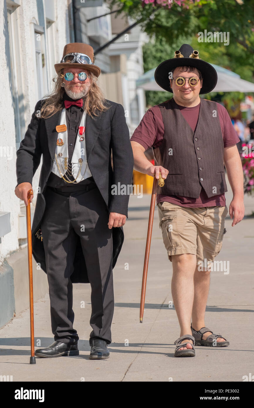 The men in costume walk down the main street in Coldwater Ontario during the annual Steampunk Festival. - Stock Image