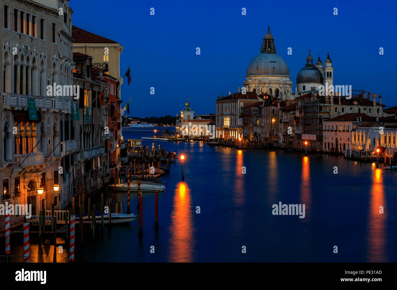 Sunset at the iconic 17th-century Santa Maria di Salute Basilica, view from Academia bridge or Puente de la academia along the Grand Canal in Venice,  Stock Photo