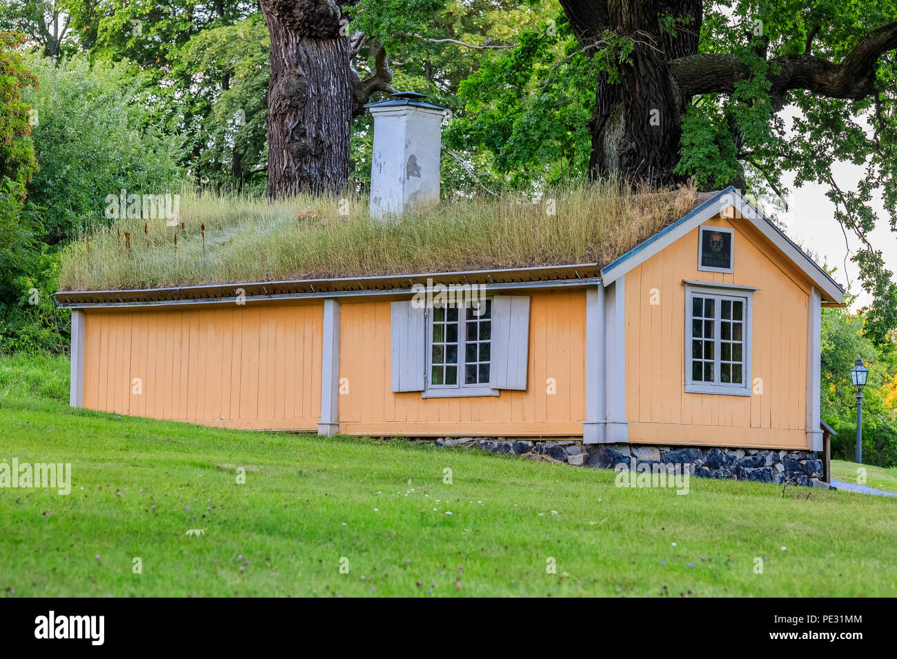 Stockholm, Sweden - August 10, 2017: Traditional Old Swedish house with a grass roof in a forest meadow - Stock Image
