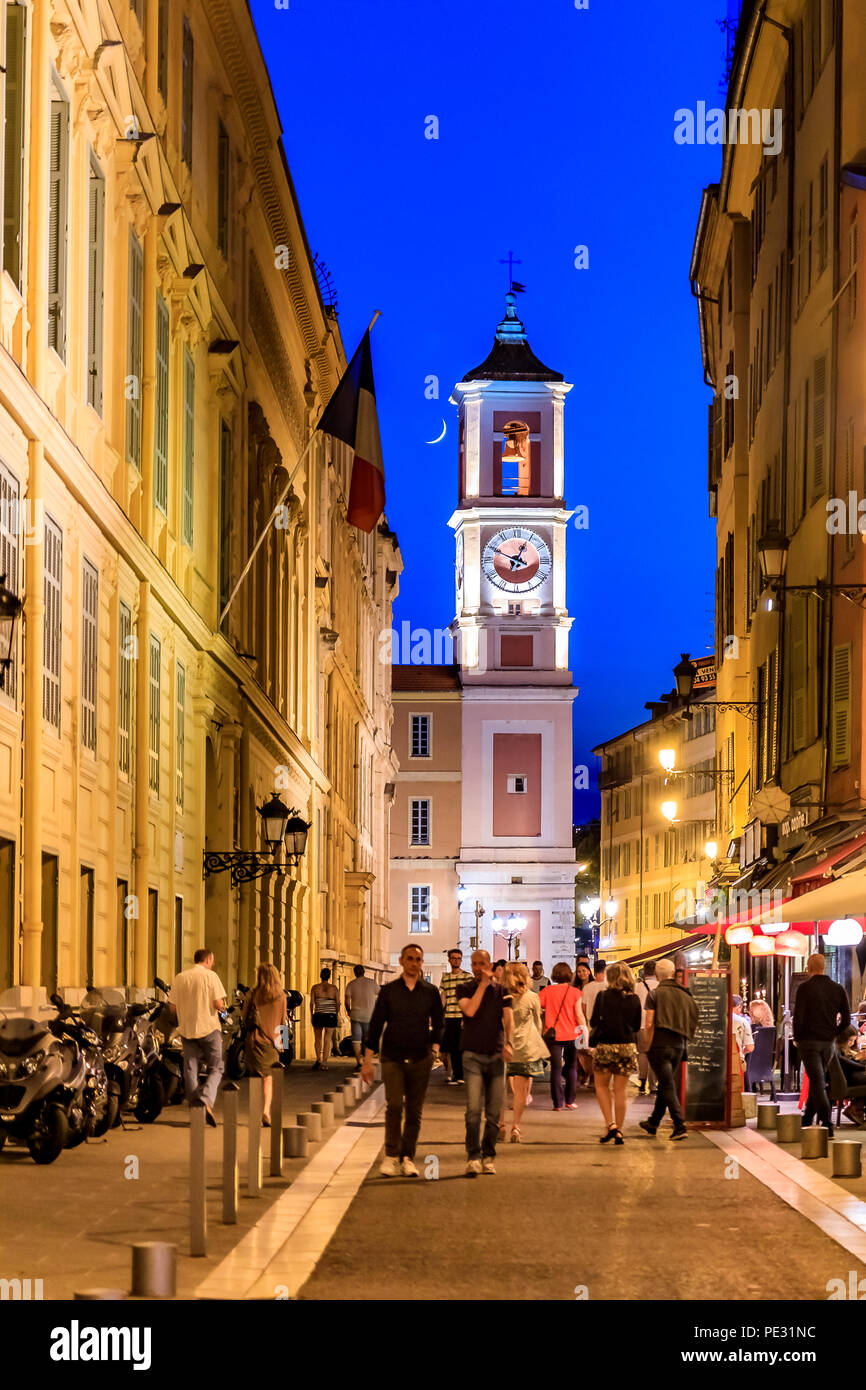 Nice, France - May 27, 2017: Crescent moon rising above the Caserne Rusca clock tower and people walking by the restaurants in the streets of the Old  - Stock Image