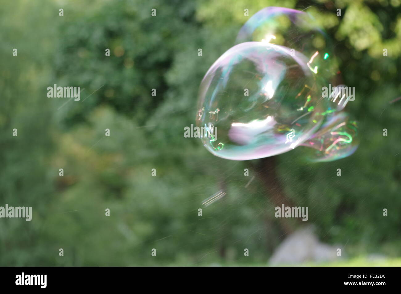 bursting bubble in the wind - Stock Image