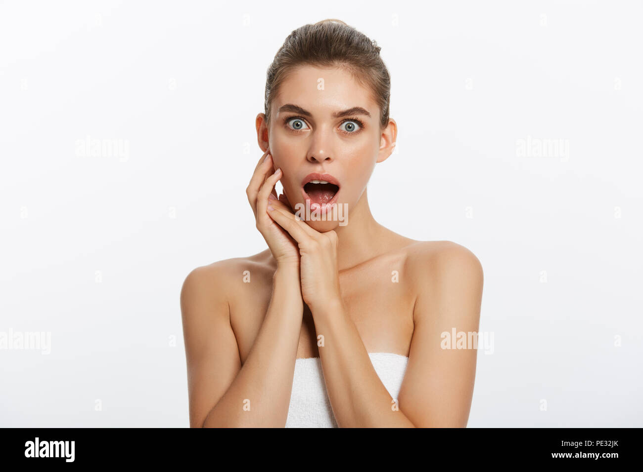 Happy beautiful girl holding her cheeks with a laugh looking to the side. Expressive facial expressions .Cosmetology and Spa - Stock Image