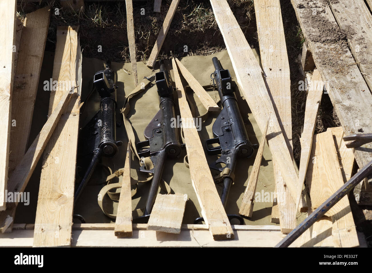 semi automatic and machine guns and rifles found hidden under decking at a house - Stock Image