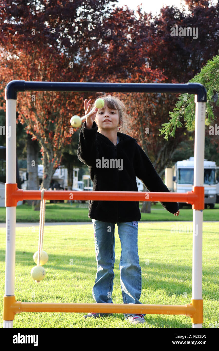 Young girl enjoying a game of ladder toss - Stock Image