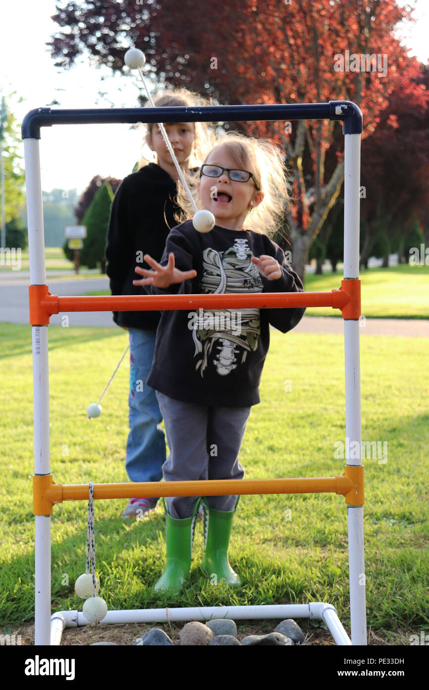 Two young girls enjoying a game of ladder toss - Stock Image