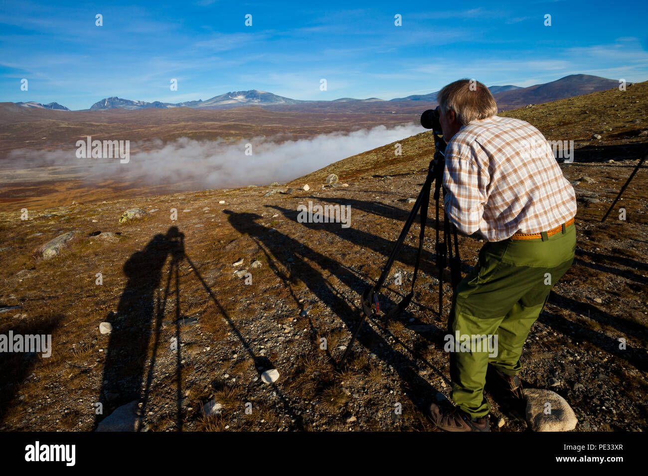An outdoor photographer is taking pictures at View Point Snøhetta in Dovrefjell national park, Dovre, Norway. - Stock Image