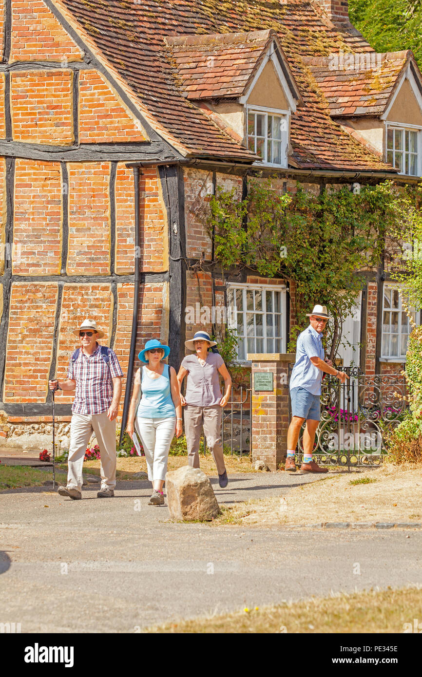Sightseers tourists and visitors leaving St Mary the virgin churchyard in the village of Turville  Buckinghamshire location for many films TV shows - Stock Image