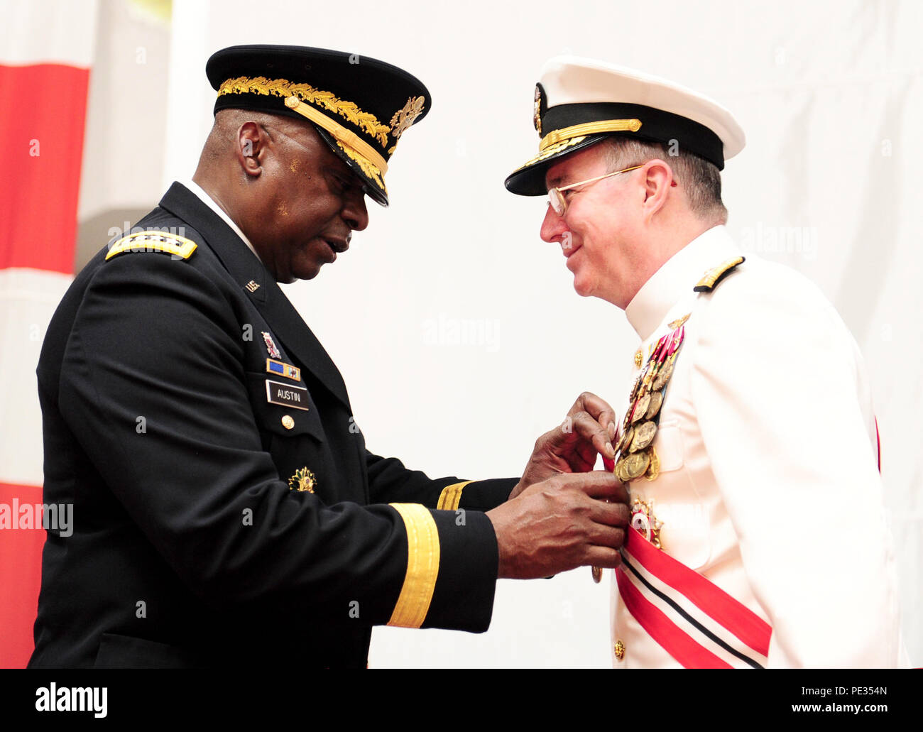 150903-N-SI600-269 MANAMA, Bahrain (Sept. 3, 2015) – U.S. Army General Lloyd J. Austin III, Commander, U.S. Central Command, awards Vice Adm. John W. Miller, outgoing commander of U.S. Naval Force Central Command/U.S. 5th Fleet/Combined Maritime Forces (NAVCENT/C5F/CMF), the Distinguished Service Medal during the NAVCENT/C5F/CMF change-of-command ceremony held aboard USS Theodore Roosevelt (CVN 71), in port here. Vice Adm. Kevin M. Donegan relieved Miller as commander of NAVCENT/C5F/CMF. (U.S. Navy photo by Mass Communication Specialist 3rd Class Anthony Hopkins/Released) Stock Photo