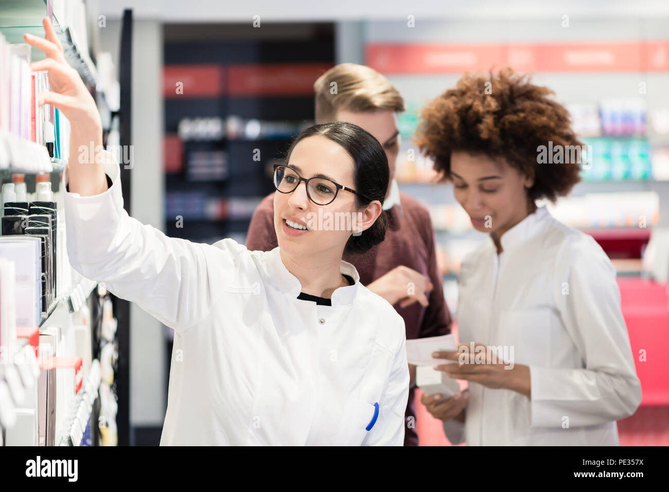 Portrait of a female experienced pharmacist reading indications - Stock Image