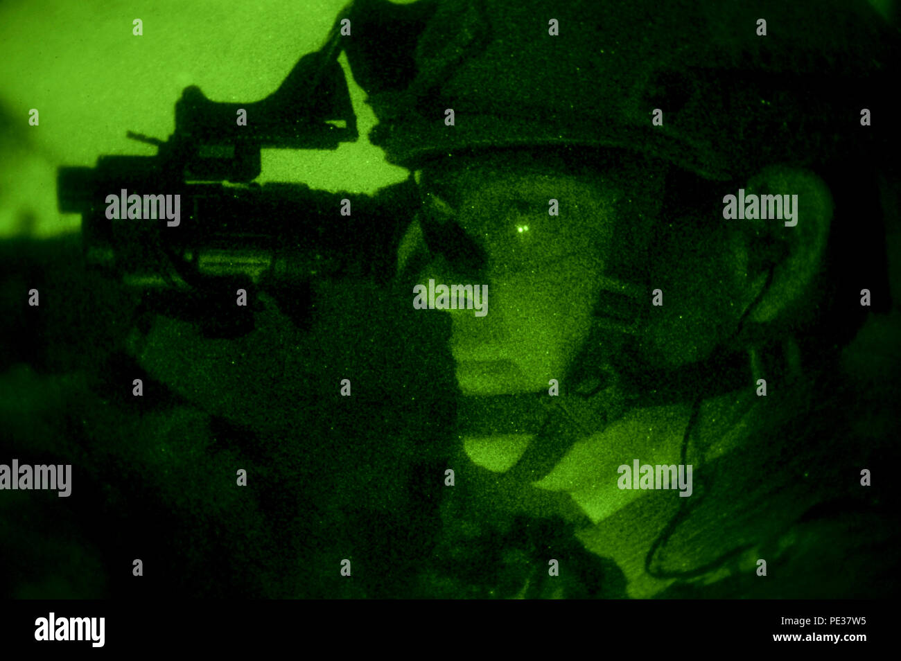 Staff Sgt. Douglas Gideon, 3rd Combat Camera Squadron, cyber transport technician, uses night vision to scan the area during a night iteration of Advanced Weapons and Tactics Training, Sept. 10, 2015, in Converse, Texas. The two-week course taught combat camera Airmen shooting fundamentals, weapons transitioning, shooting on the move and engaging threats in low-light conditions. (U.S. Air Force photo by Senior Airman Colville McFee) - Stock Image