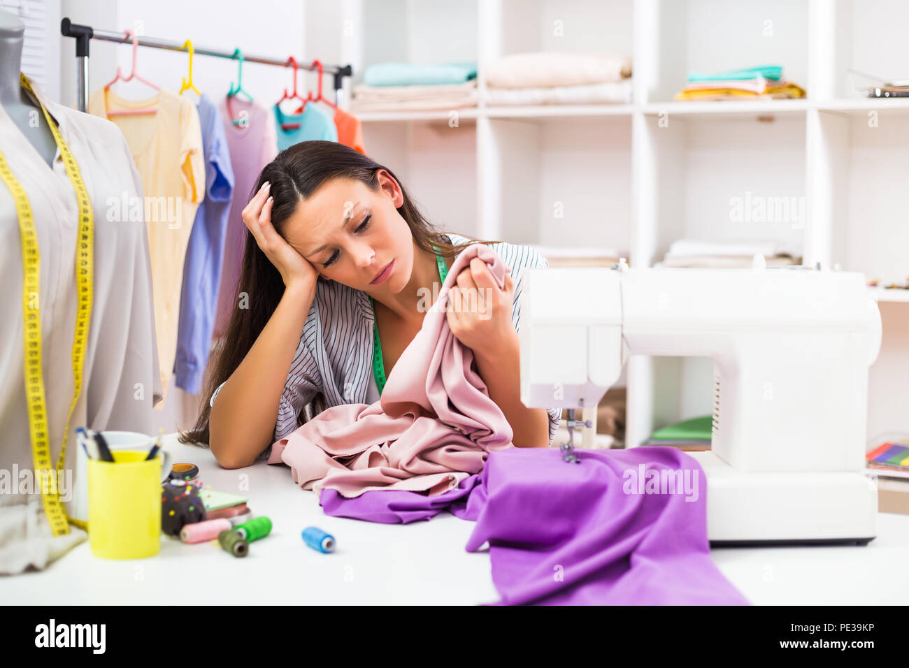 Seamstress has made a mistake while working at her workshop. - Stock Image