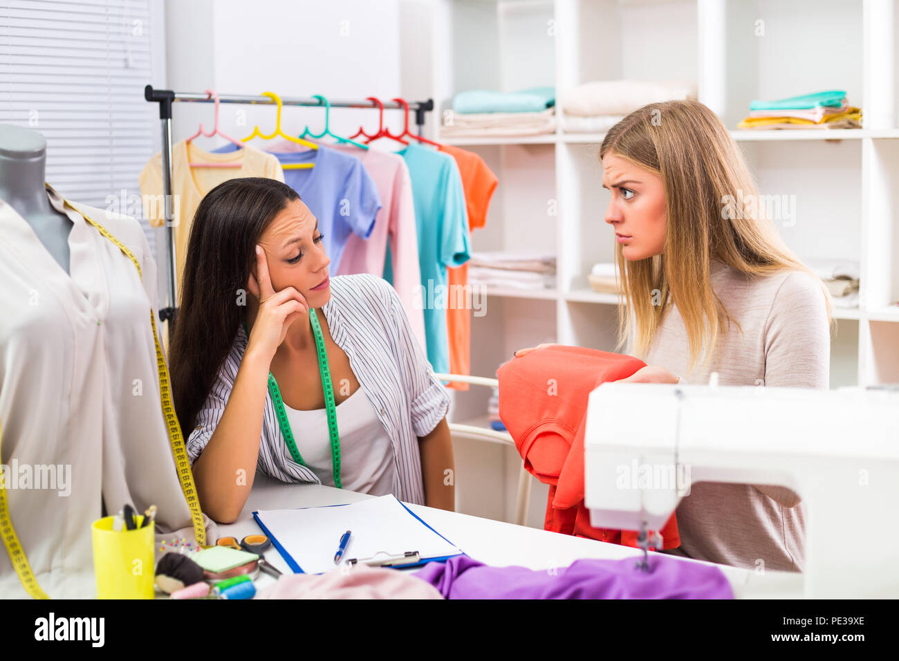 Unsatisfied customer and seamstress having conflict. - Stock Image