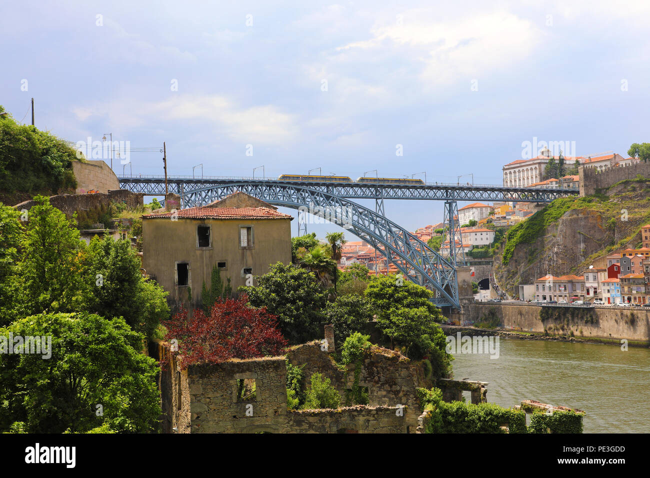 Dom Luis I bridge with tram passing and Douro River with old ruins in foreground, Porto, Portugal - Stock Image
