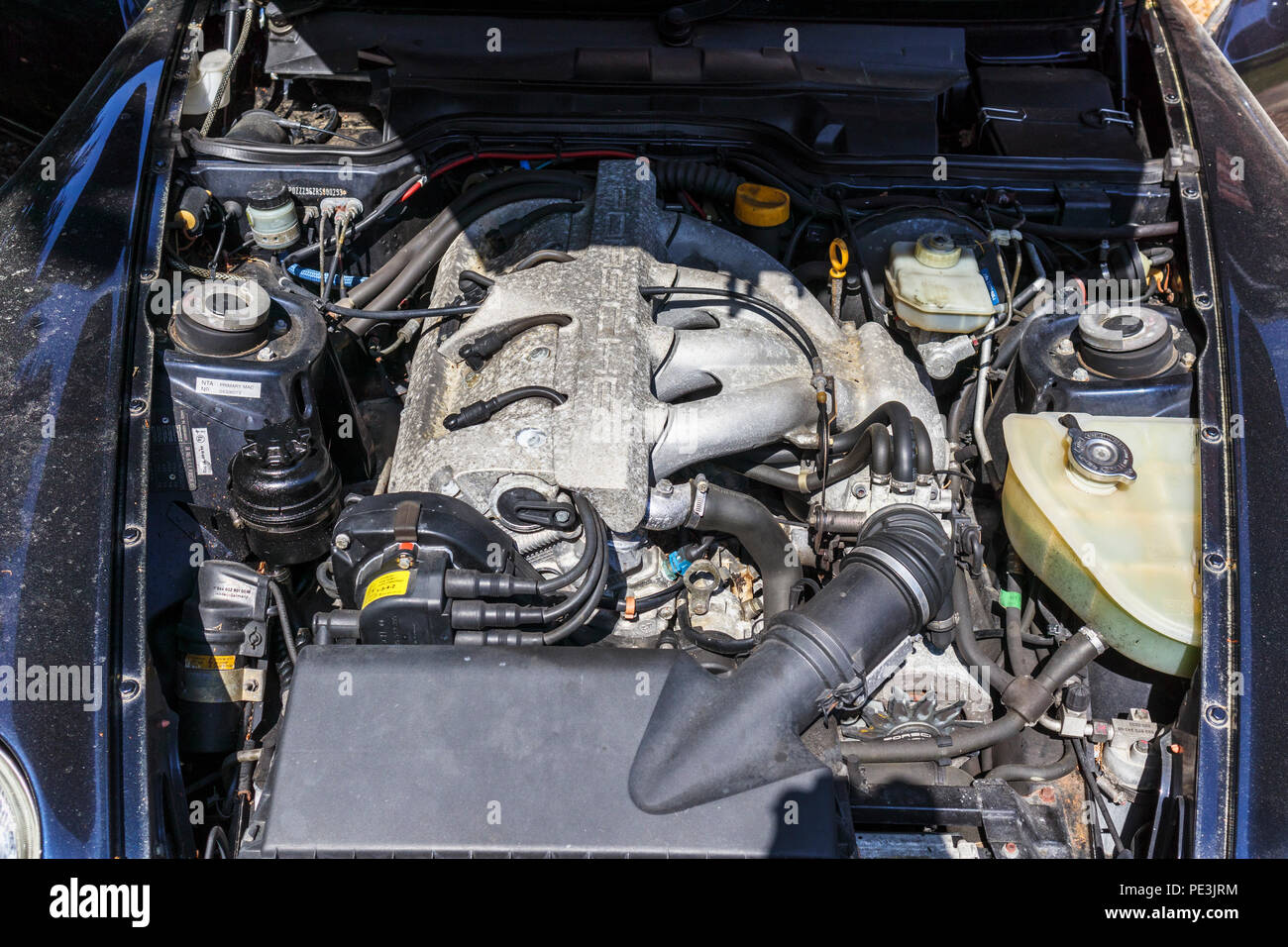 Open bonnet (hood) of a vintage Porsche 968 and the 3 litre straight-four engine (Front longitudinal inline four cylinder water cooled 16v VarioCam) Stock Photo