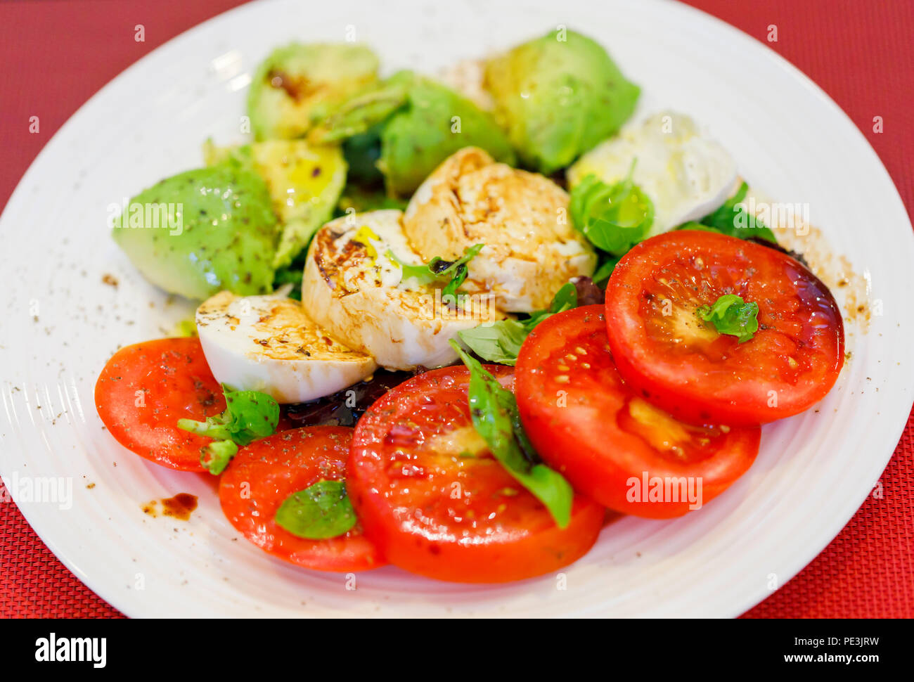 Healthy lifestyle: typical Mediterranean diet, tricolore salad ingredients sliced red tomatoes, white buffalo mozzarella cheese and green avocado pear - Stock Image