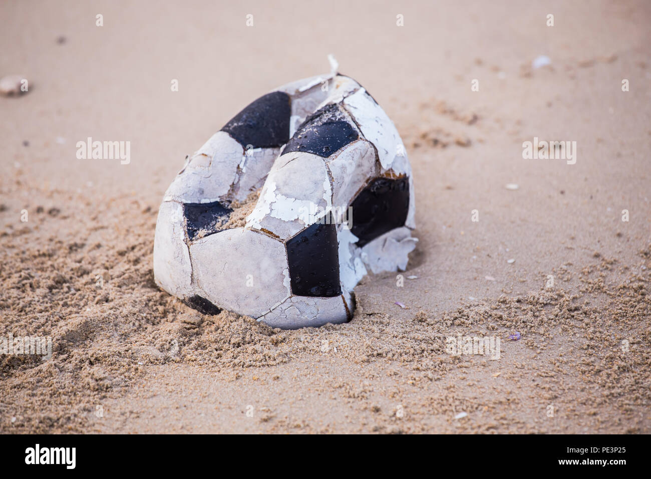 Football old, torn and dirty marks were left on the beach. - Stock Image