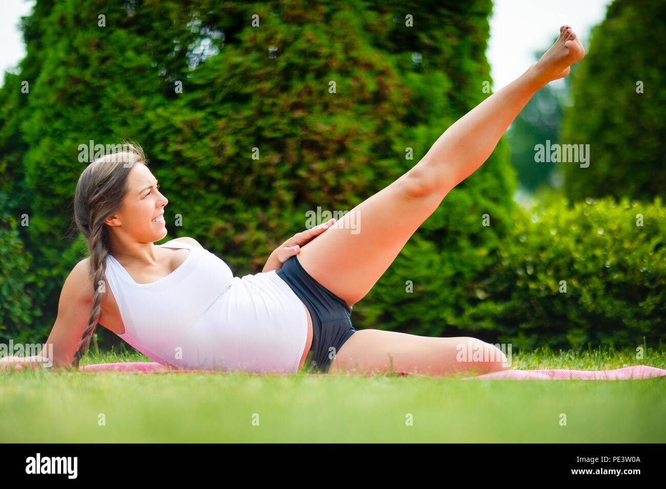 Expectant Woman Performing Side Reclining Leg Lift On Yoga Mat - Stock Image