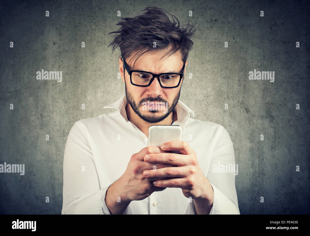 stunned man, surprised offended, shocked by what he sees on his smartphone - Stock Image