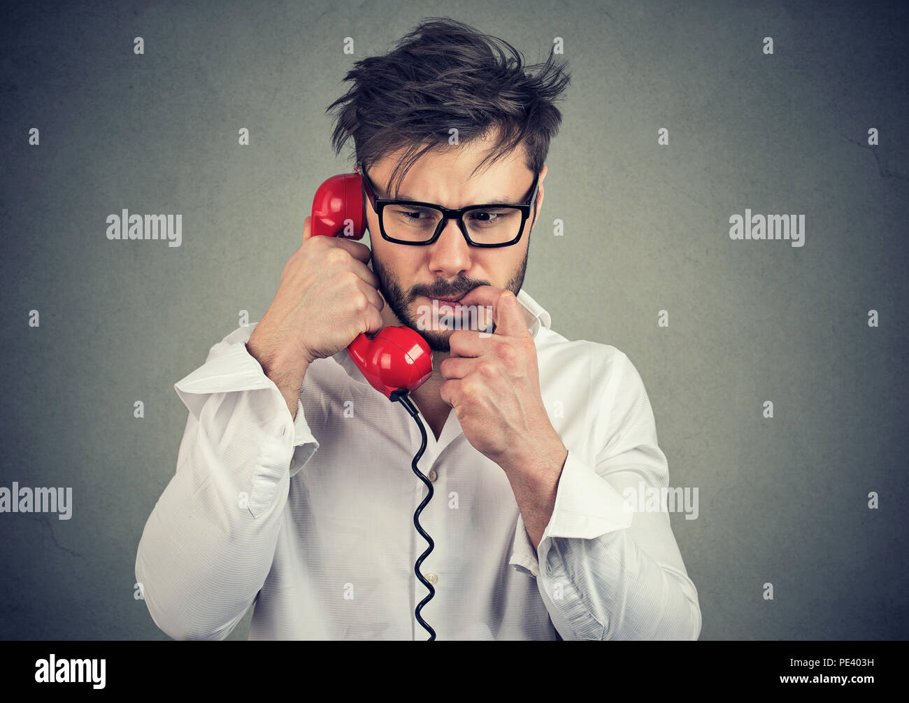 Young frustrated man in glasses having call on telephone and biting nail looking nervous while speaking on gray background - Stock Image