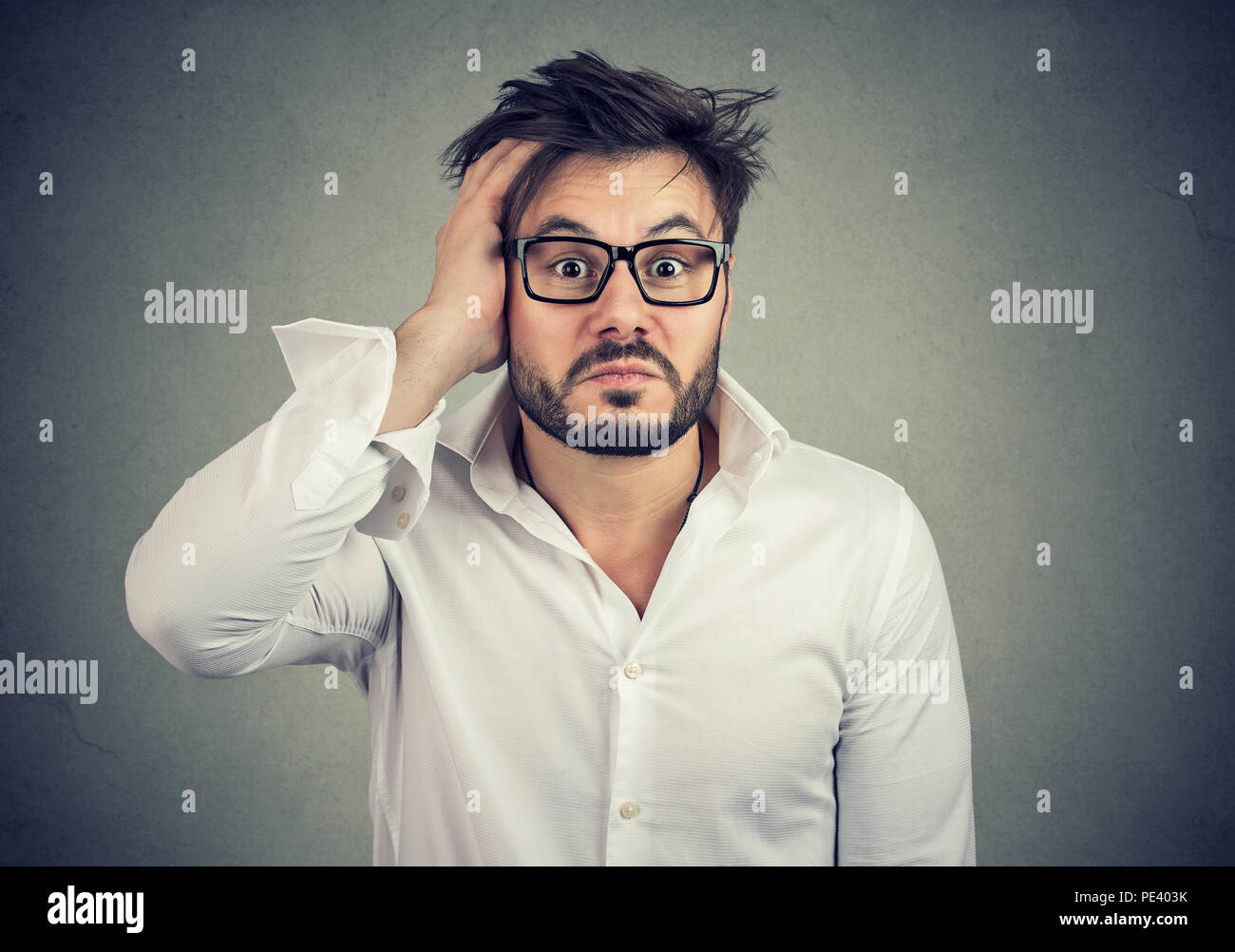Young lost and dumbfounded man with hand on head wearing glasses and looking perplexed at camera on gray background - Stock Image