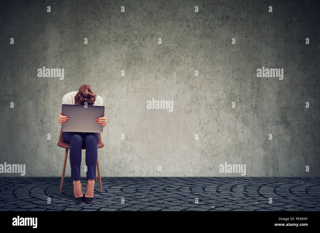 Anonymous woman sitting on chair with laptop on knees and looking desperate in crisis against gray wall background - Stock Image
