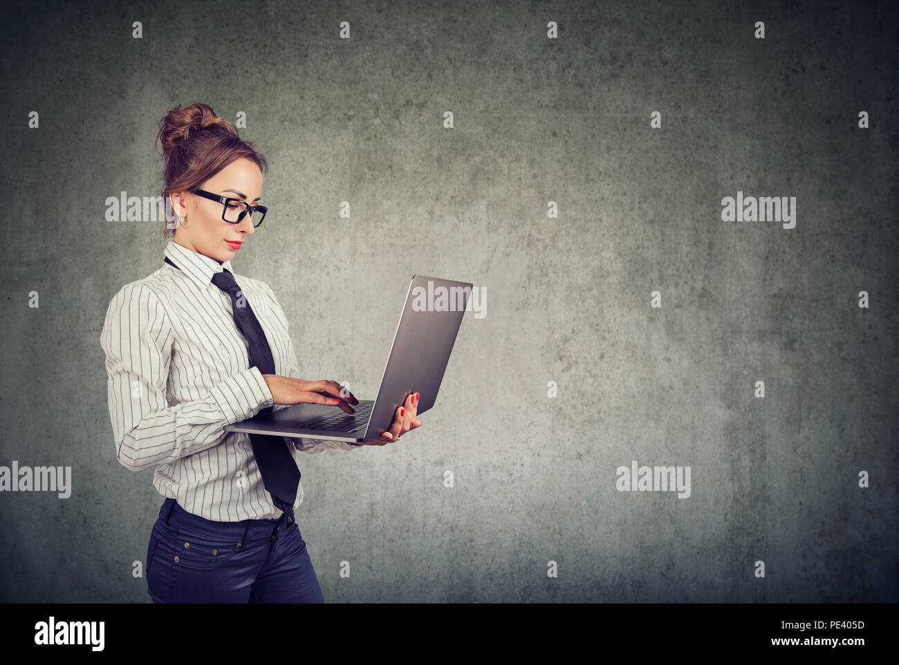 Serious professional woman in formal outfit and glasses using laptop and working against gray wall background - Stock Image
