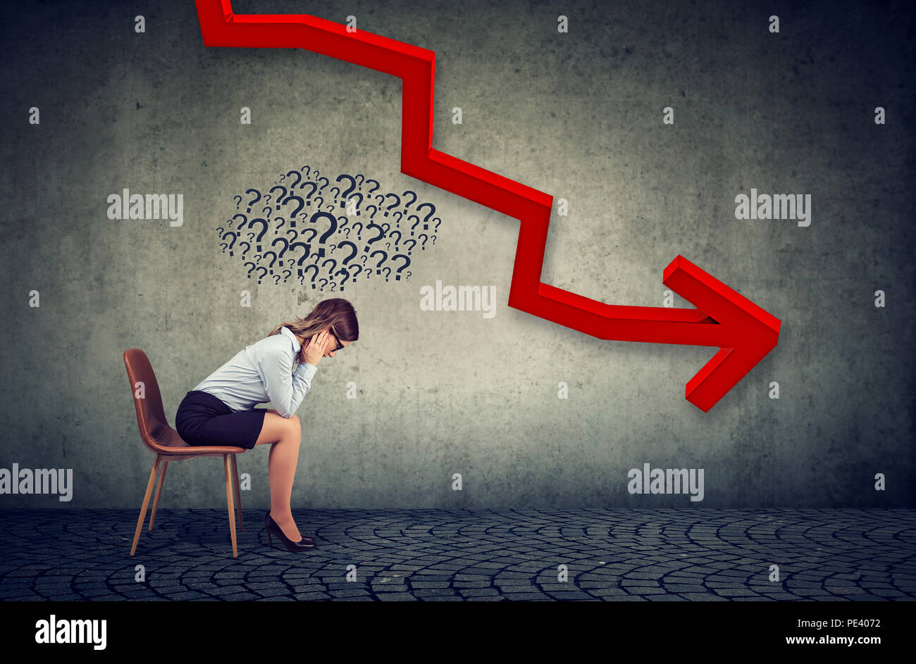 Depressed business woman looking down at the falling red arrow feeling confused has many questions. Fall and depreciation concept. - Stock Image