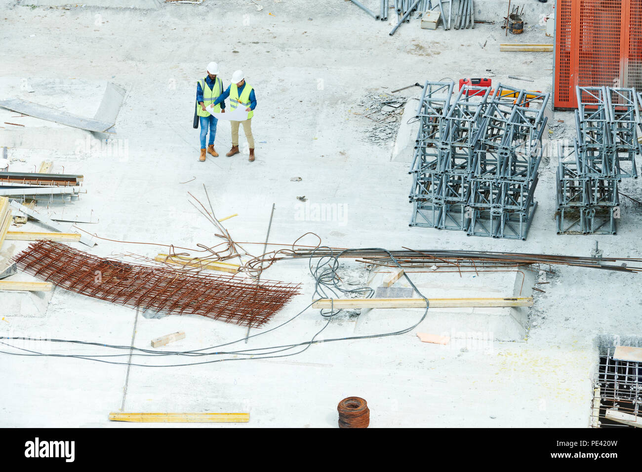 Engineers on reading blueprint on construction site Stock Photo