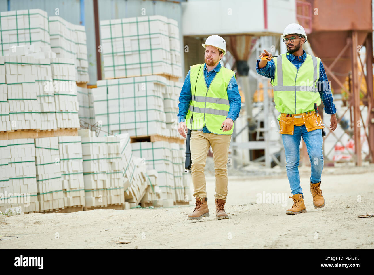 Building inspectors walking on construction site - Stock Image