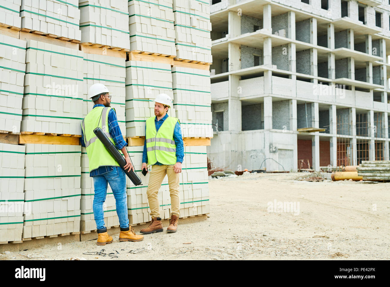 Construction engineers speaking near materials - Stock Image