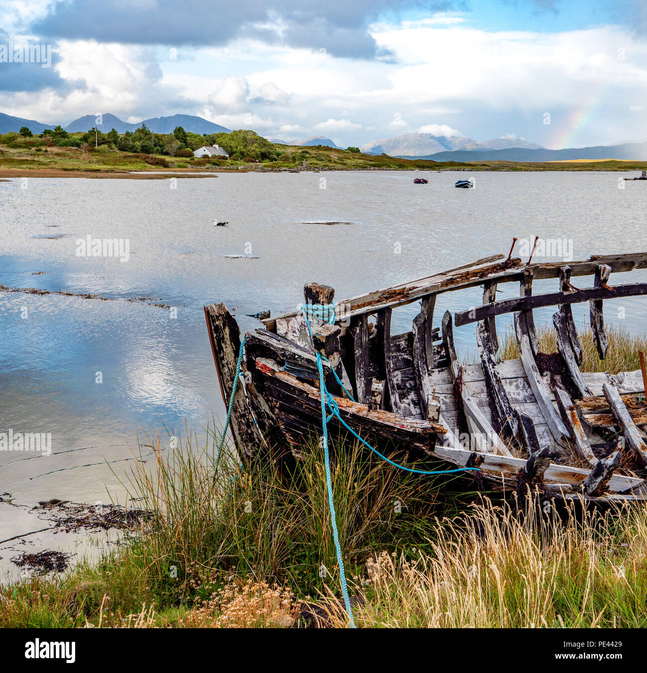 Prow of a wrecked boat with Twelve Bens beyond on the island if Inishnee near Roundstone on the coast of Connemara Ireland - Stock Image