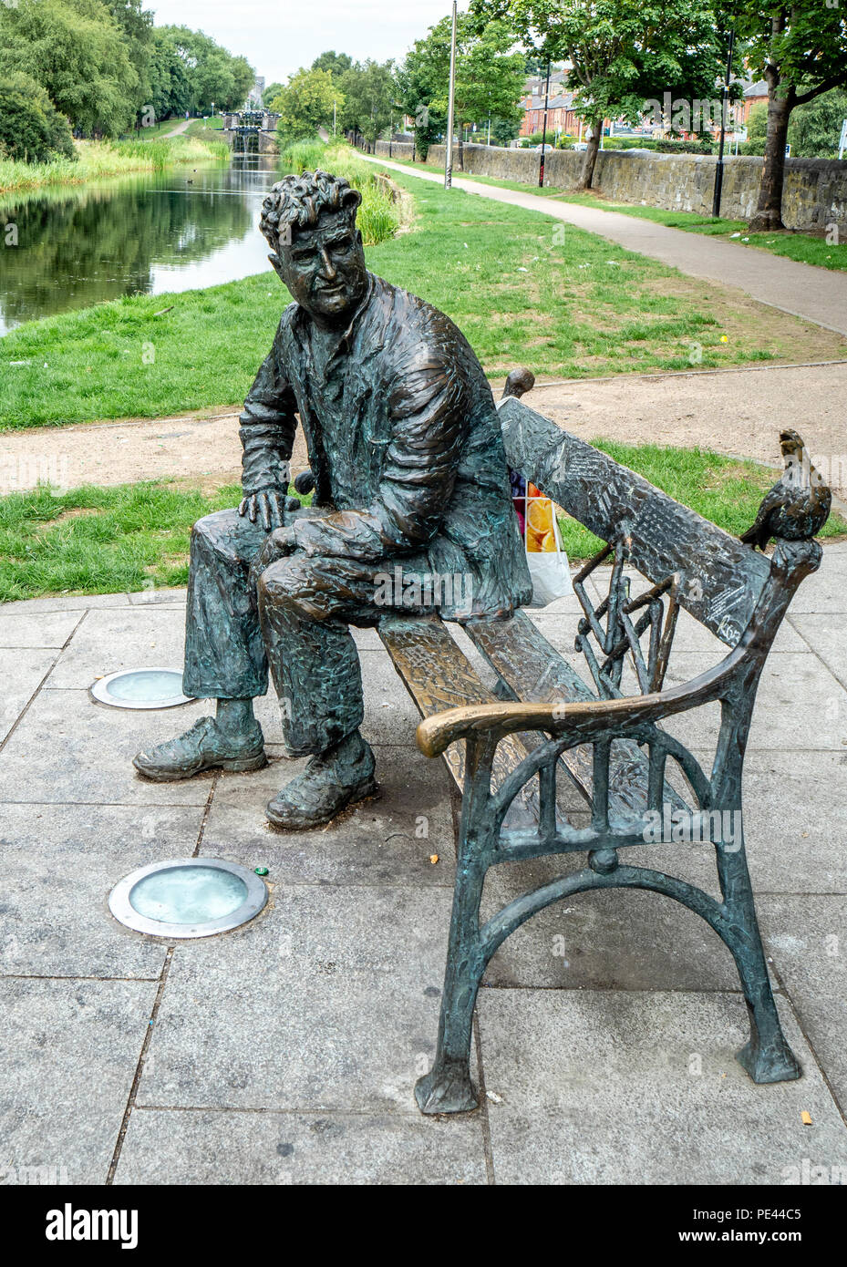 Bronze sculpture of novelist and playwright Brendan Behan and pigeon on a park bench by the Royal Canal in Dublin Ireland - Stock Image