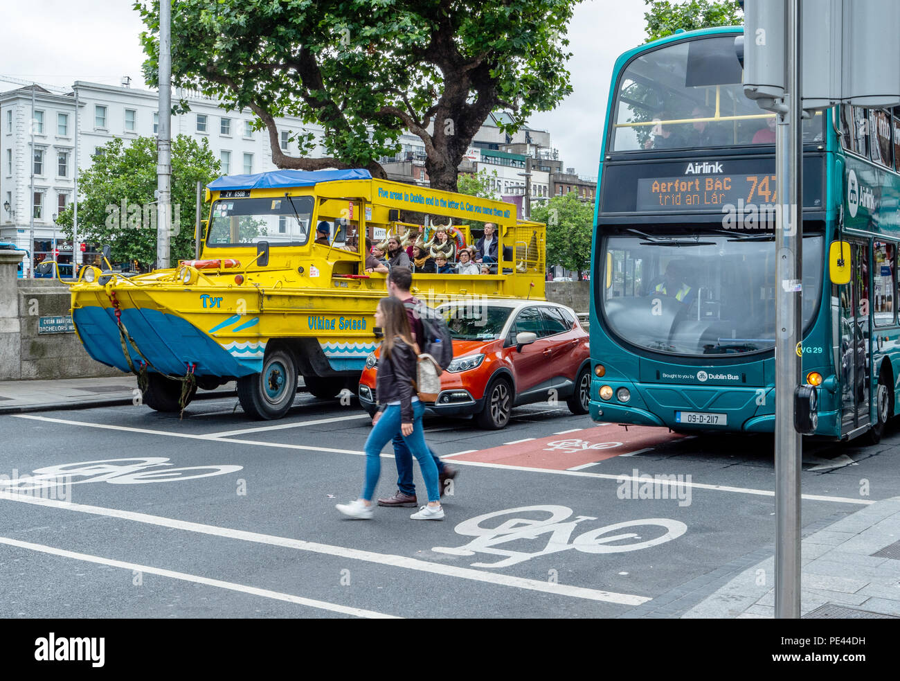 The Duck Tours amphibious vehicle waiting at a pedestrian crossing with a car and bus in the centre of Dublin Ireland - Stock Image