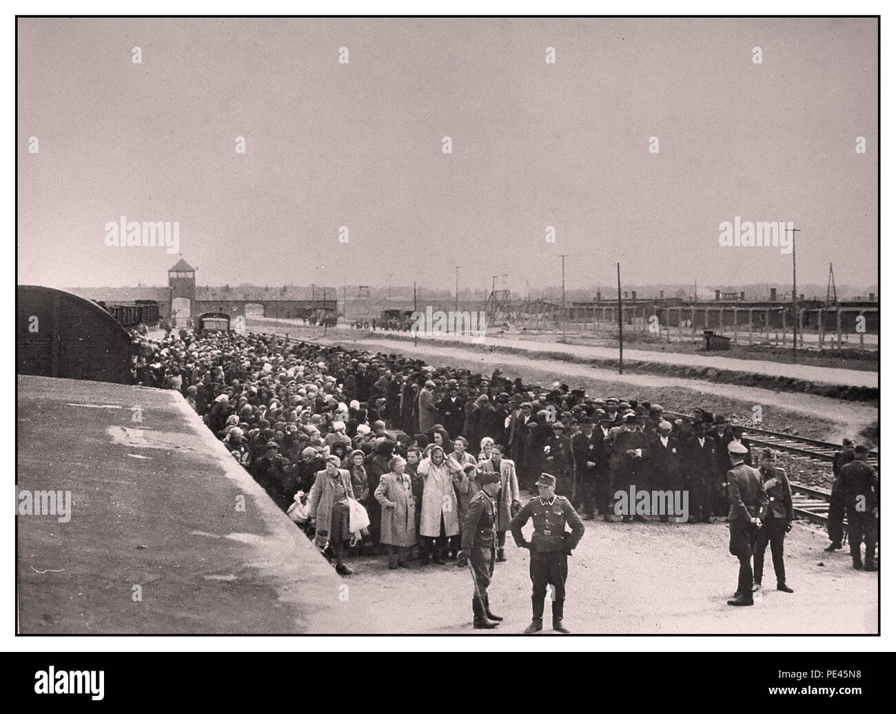 AUSCHWITZ-BIRKENAU PRISONERS ARRIVAL- A vision of hell on earth. 1944, Nazis 'grading' (life or death) unsuspecting prisoners on rail concourse outside entrance to Auschwitz-Birkenau extermination death camp. The infamous Auschwitz camp was started by order of Adolf Hitler in 1940's during the occupation of Poland by Nazi Germany during World War 2, further enabled by Heinrich Luitpold Himmler the Reichsführer of the Schutzstaffel, and leading member of the Nazi Party of Germany - Stock Image