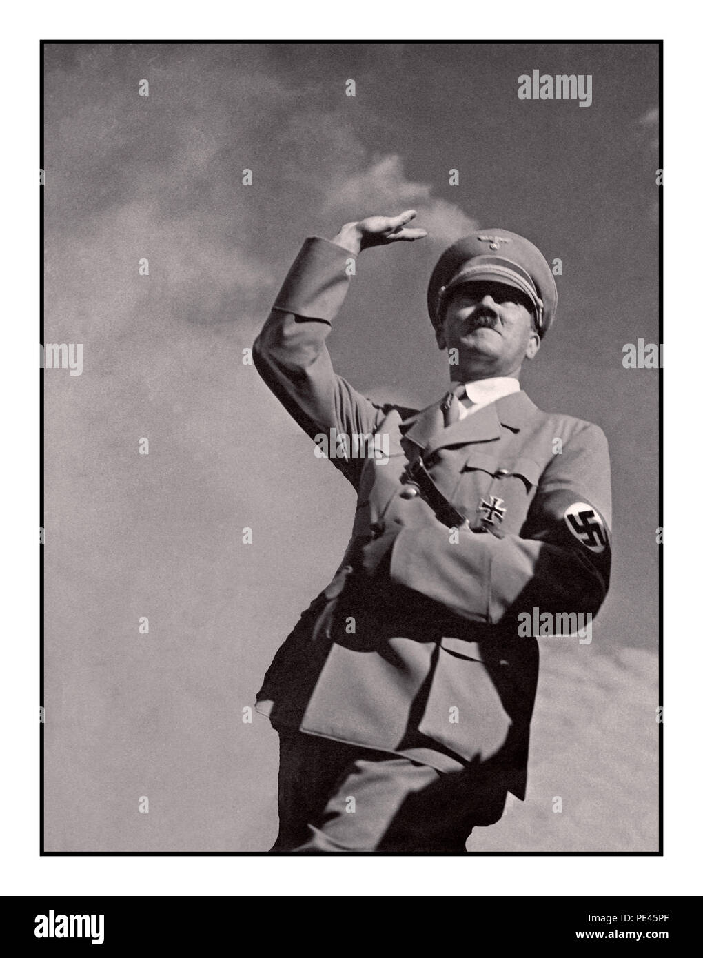 ADOLF HITLER SALUTE 1939 WW2 German propaganda  image of Adolf Hitler in military uniform wearing a Nazi swastika armband saluting 'Heil Hitler' to a crowd low angle view with sky background - Stock Image
