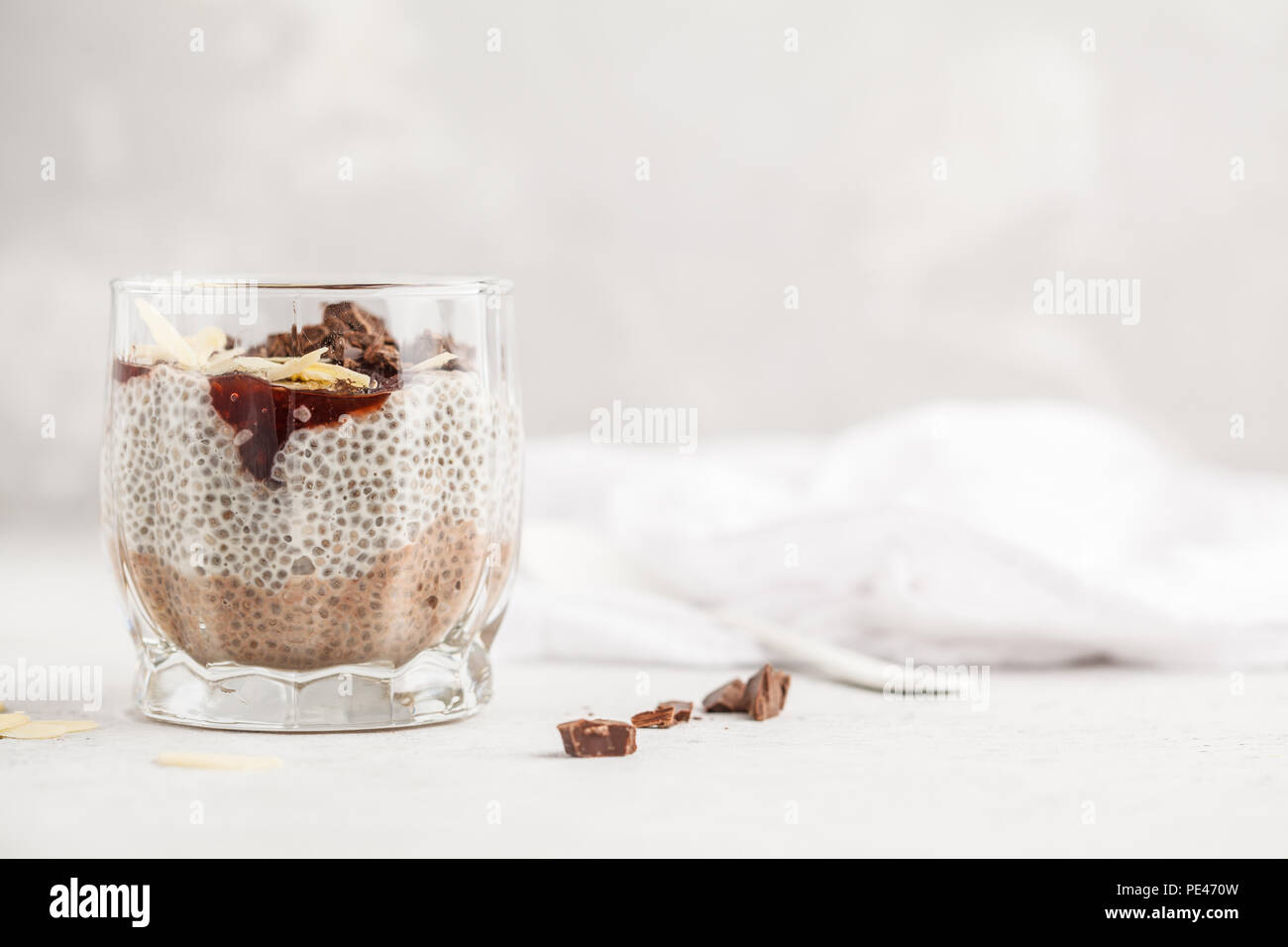 Chia pudding with chocolate, almonds and berry jam, white background. Raw vegan dessert. Clean eating concept. - Stock Image