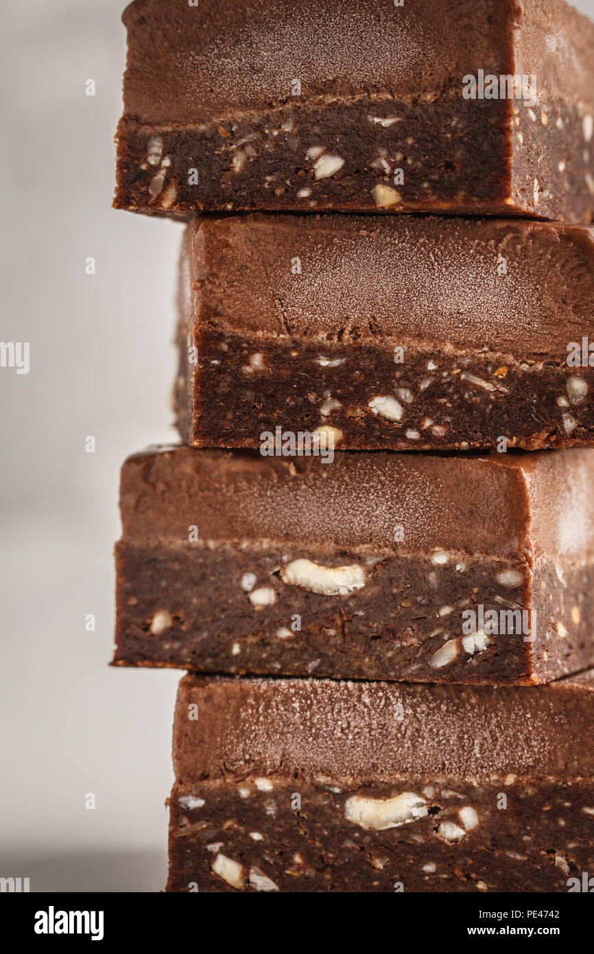 Stack of chocolate fudge bars on white background. Clean eating concept. Raw vegan dessrt. - Stock Image