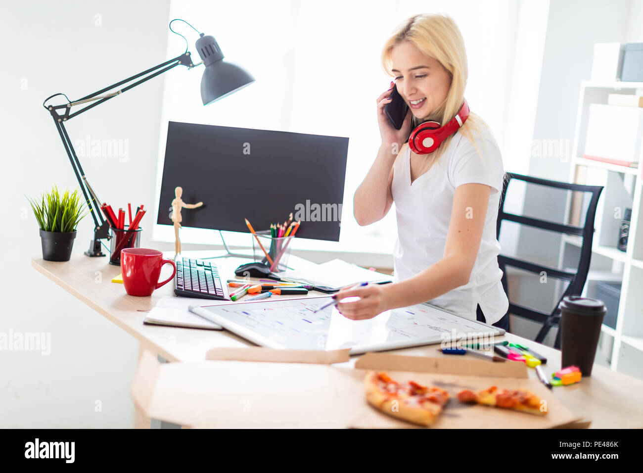 A young girl is standing near a table, talking on the phone and holding a marker in her hand. On the table is a magnetic board. On the neck, the girl's headphones hang. - Stock Image