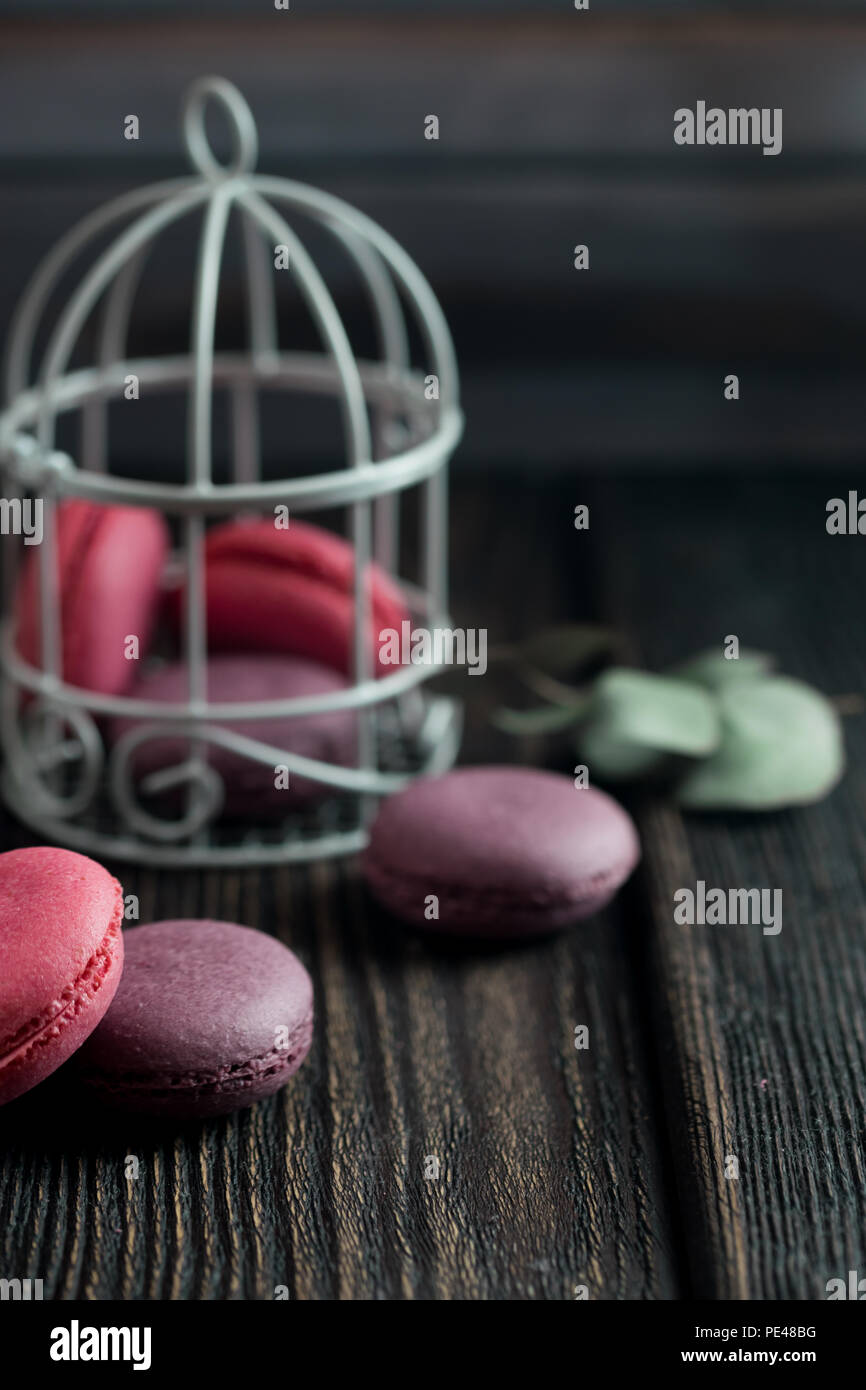 Group of macarons made of strawberries, cream, chocolate and blueberries. Rustic photo. Toned. - Stock Image