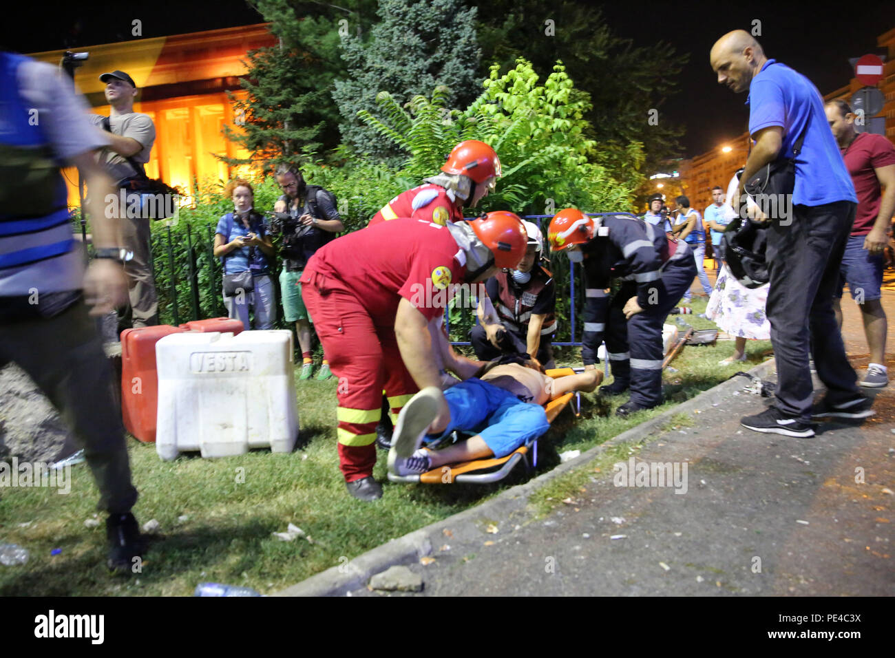 Bucharest, Romania - August 10, 2018: Paramedics are offering first aid to an injured football supporter by tear gas receives during the violent anti- - Stock Image