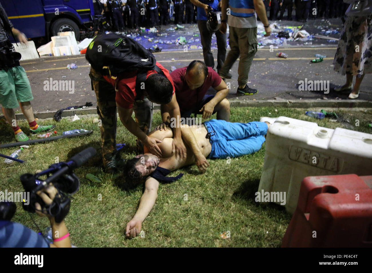Bucharest, Romania - August 10, 2018:  An injured football supporter by tear gas receives help during the violent anti-government protest in Bucharest - Stock Image