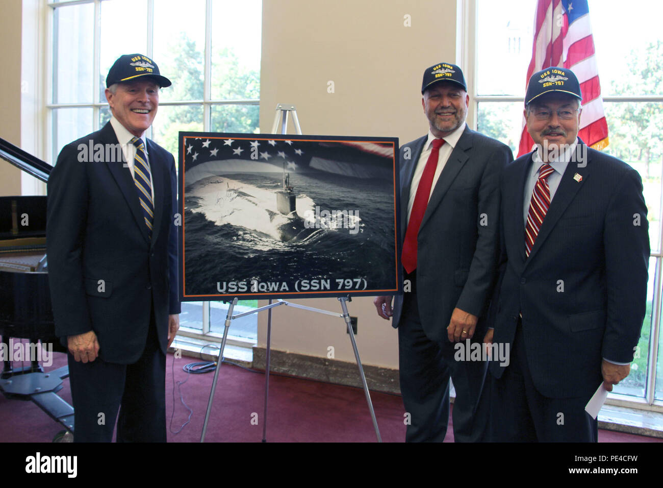 AMES, Iowa, (Sept. 2, 2015) -- From left: Secretary of the Navy (SECNAV) Ray Mabus, Iowa State President Steven Leath and Iowa Gov. Terry Branstad stand next to a graphic representation of the Navy's newest Virginia-class attack submarine, the future USS Iowa (SSN 797) at Iowa State University in Ames, Iowa. Mabus thanked the people of Iowa for their support and contributions to the Navy and discussed the special bond that exists between a state and its namesake vessel. (U.S. Navy photo courtesy of ISU NROTC/Released) Stock Photo