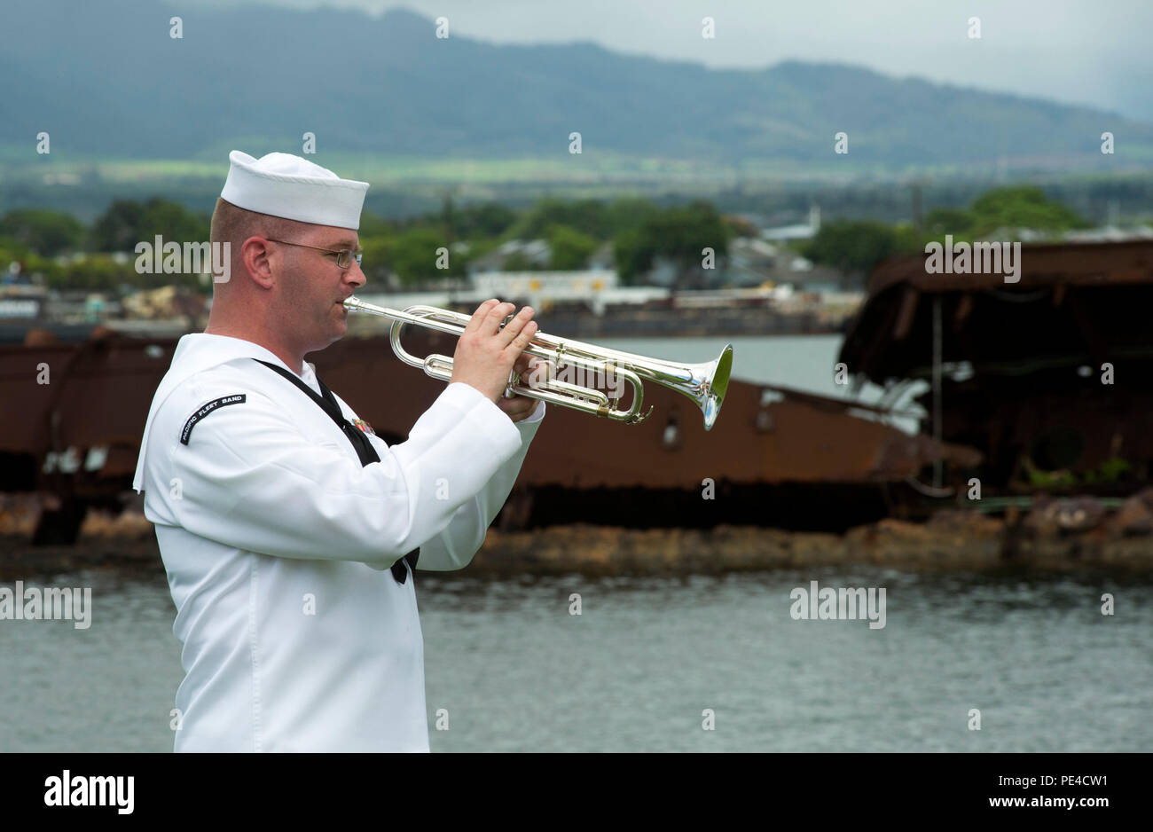 150909-N-GI544-046 PEARL HARBOR (Sept. 9, 2015) Musician 1st Class Peter Sutorius, assigned to Pacific Fleet Band, plays taps during an ash-scattering ceremony for the late Pearl Harbor survivor U.S. Navy Chief Petty Officer Daryl L. Finch at the USS Utah Memorial on Ford Island, Joint Base Pearl Harbor-Hickam. Finch was serving on Ford Island during the 1941 Japanese attacks on Pearl Harbor. His ashes joined the remains of Sailors still aboard USS Utah, which was sunk during the 1941 attack. (U.S. Navy photo by Mass Communication Specialist 2nd Class Laurie Dexter/Released) Stock Photo