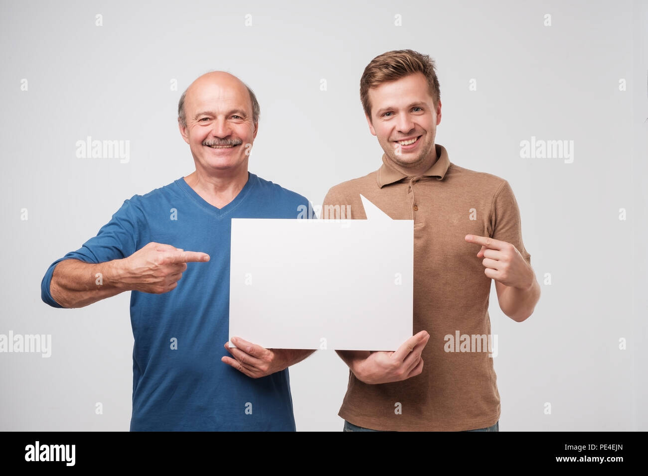 Two mature men father and son are holding a white empty billboard together. The friends are standing and smiling. Pay attention to profitable proposit - Stock Image