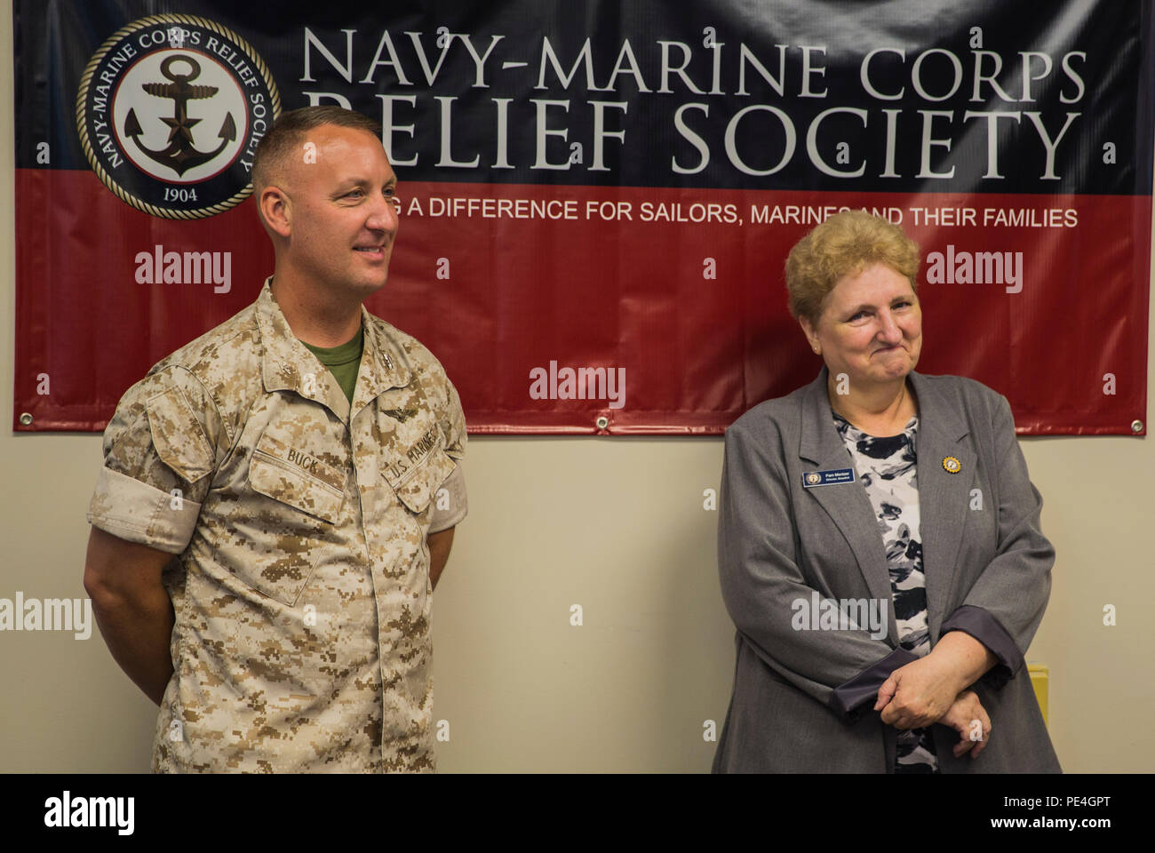 Col. Peter D. Buck congratulates Pam Mentzer during a celebration of her 20-year anniversary of employment with the Navy Marine Corps Relief Society aboard Marine Corps Air Station Beaufort Sept. 1, 2015. Her history of volunteer work with NMCRS goes back to 1980.  Mentzer is the director of NMCRS aboard the air station. Buck is the commanding officer of MCAS Beaufort. - Stock Image