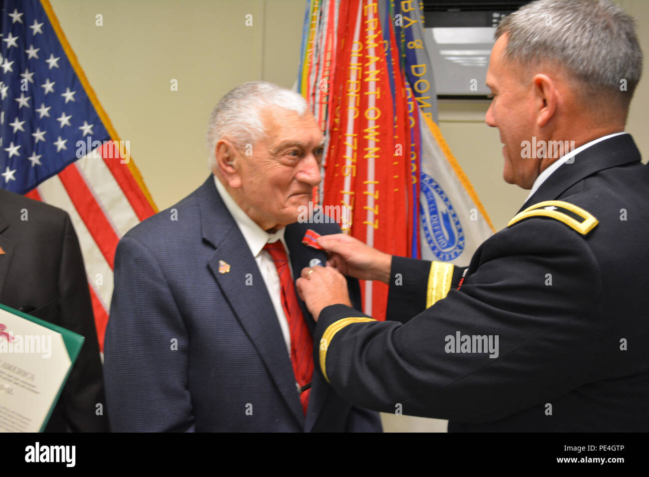 Brig. Gen. Steven Ainsworth, commander 94th Training Division, awards the Bronze Star medal to WWII veteran Technician 4th Class, retired, Vincenzo Geramita during an intimate ceremony filled with family, friends and service members at Fort Dix, N.J., Sept. 12, 2015. Geramita and Lt. Col., retired, Andrew Cella each received the medal after 70 years because after they earned their Combat Infantry Badges for the fighting they experienced in Europe, neither one knew that a 1947 general order made them eligible for the Bronze Star since they had earned their CIBs between 1941 and 1945. - Stock Image