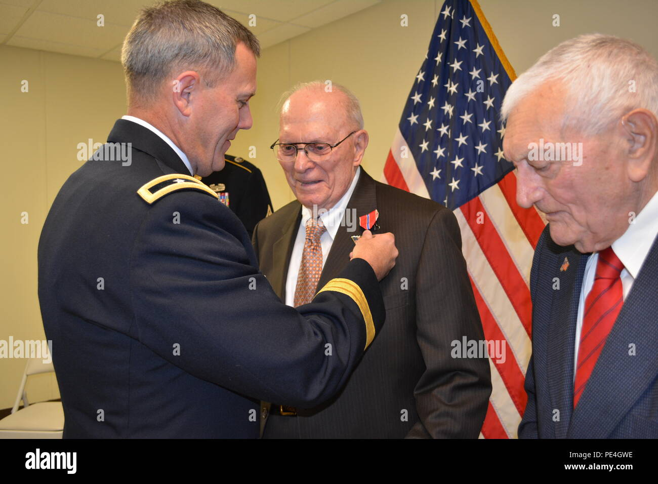 Brig. Gen. Steven Ainsworth, commander 94th Training Division, awards the Bronze Star medal to WWII veteran Lt. Col., retired, Andrew Cella during an intimate ceremony filled with family, friends and service members at Fort Dix, N.J., Sept. 12, 2015. Cella and Technician 4th Class, retired, Vincenzo Geramita (Right) each received the medal after 70 years because after they earned their Combat Infantry Badges for the fighting they experienced in Europe, neither one knew that a 1947 general order made them eligible for the Bronze Star since they had earned their CIBs between 1941 and 1945. - Stock Image