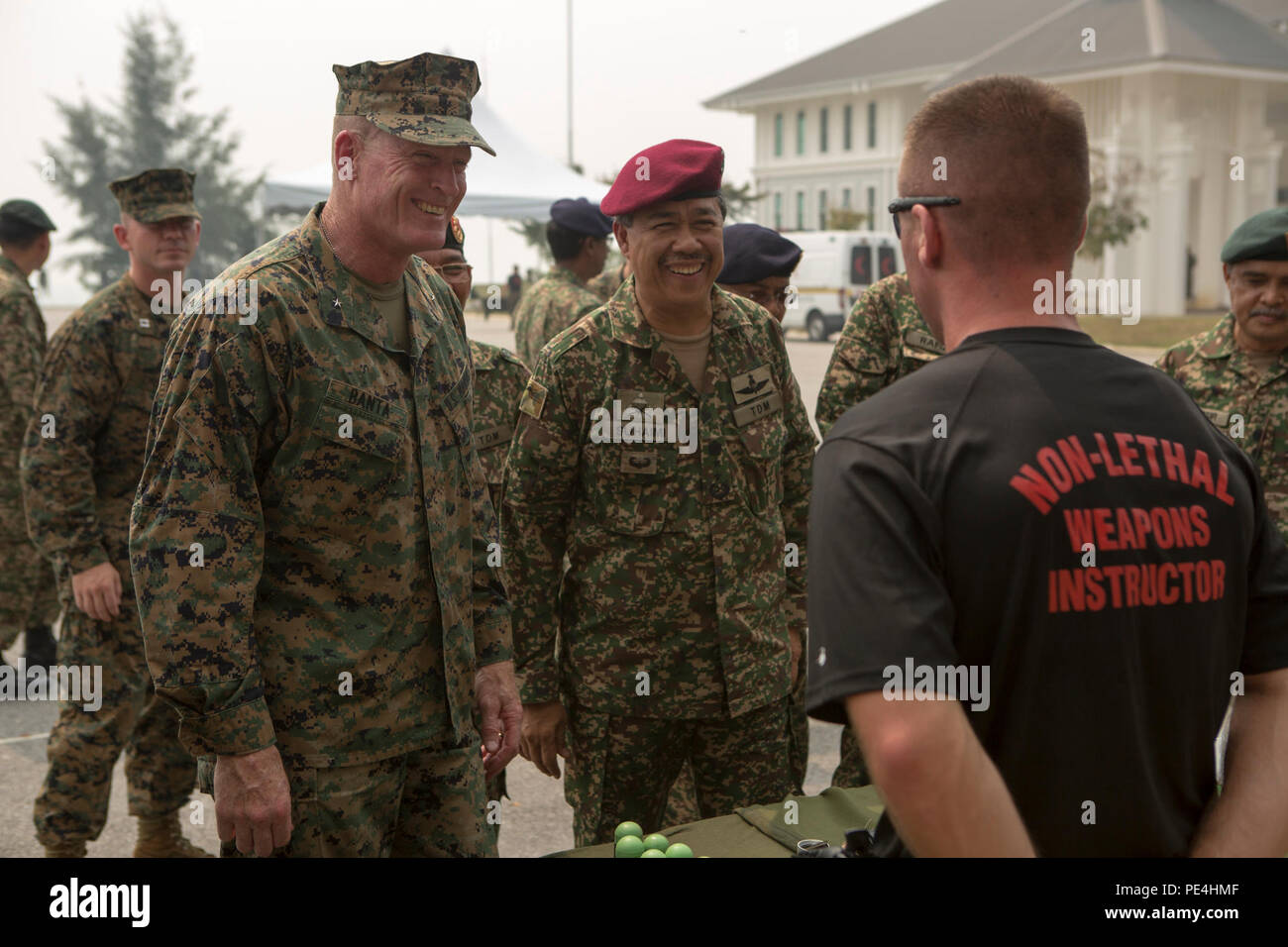 Maj. Gen. Dato' Mohd Suhaimi bin Hj Mohd Zuki, commanding general of the Malaysian Army Training and Doctrine Command, and Brig. Gen. Edward D. Banta, commanding general of Marine Corps Installations West, speak to Sgt. Christopher Nowlin, a non-lethal weapons instructor with 3rd Law Enforcement Battalion, III Marine Expeditionary Force, during Non-lethal Weapons Executive Seminar, Sept. 16, 2015. NOLES is an annual exercise hosted by U.S. Marine Corps Forces, Pacific and is the U.S. Pacific Command's premier multilateral theater security cooperation event for non-lethal weapons, this is the 1 Stock Photo